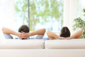 Rear view of a couple relaxing on a sofa at home and looking outside a green background through the window of the living room